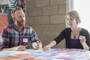 Joe Hankins sits with another CoLED participant at a table, working together toarrange notes during a workshop.