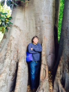 George Marcus, a white man with brown-grey hair, is wearing a blue jacket and blue jeans, and standing comfortably with his arms folded across his chest, leaning back against a very large tree. The trunk of the tree is wider than he is tall.