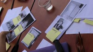 black and white print outs of photos gathered from passerby cellphones are on a table with a glass of water and a pair of sunglasses. yellow sticky notes with handwritten words like 'memory' and 'efficientcy' are stuck to the papers. a woman's hand with a silver thumb ring picks up one of the papers.