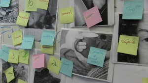 A series of stock photo images and collected photos printed in black and white are stuck to a white board, and three colors of sticky notes with handwritten numbers and descriptive words like 'skeptical' 'nostalgia' 'sharing' and 'immoral' are stuck on top of the black and white images.
