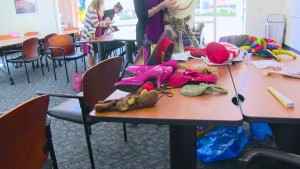A variety of colorful objects laid out on a table - pink high heels, a red hat, a leopard print something, some musical instruments, etc in a classroom-like environment.