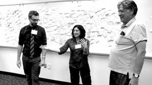 Keith, Elana, and George stand in front of a white board covered in sticky notes. Elana gestures while speaking, and Keith and George look at her.