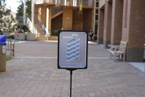 "An image taken from the conference program showing an art piece with a geometrically arranged tapemeasure and the words ""formal play"" stands in a temporary display sign on a brick walkway on the UC Irvine campus. The social sciences building and several students walking across the square are out of focus in the background."
