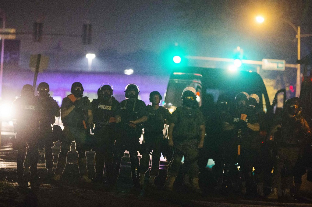 Police officers line up across the street as they maintain their distance from protesters during on-going demonstrations to protest against the shooting of Michael Brown, in Ferguson
